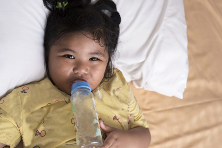 Adorable baby girl holding milk bottle and drinking on the bed in bedroom Standard-Bild