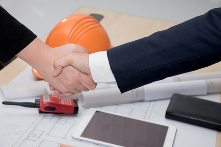 Two confident Businessman and businesswoman shaking hands over a deal signing a contract