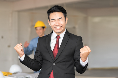 Celebrating success with excited young businessman keeping arms raised and expressing positivity while standing inside building construction site background Standard-Bild