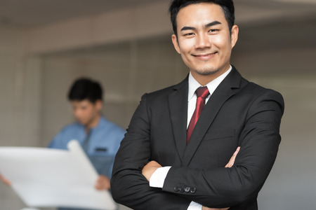 Portrait of handsome confident young businessman standing arms crossed, smiling happy, looking at camera over construction site background