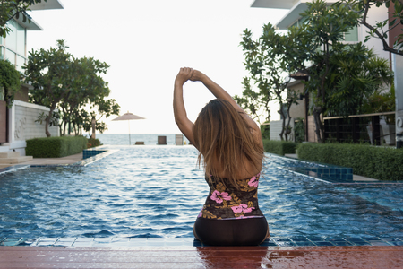 Woman sitting on swimming pool in tropical beach resort with lounge chairs and umbrella, Sea view, Thailand, Relax and Travel Concept Stock Photo
