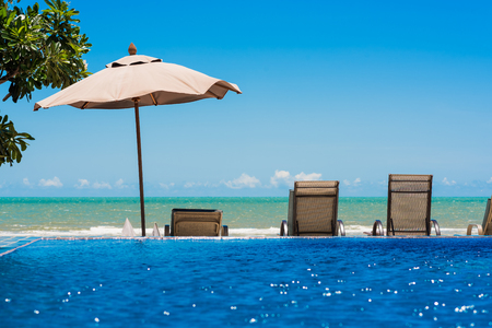 Tropical beach resort with lounge chairs and umbrella