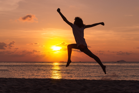 Freedom concept with young teenager happy and jump over a beautiful sunset on the beach