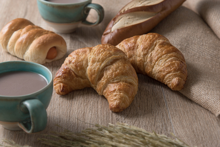 Croissants with bread and coffee cup on wooden background Stock Photo