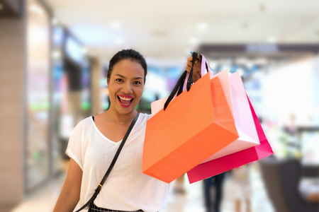 Shopping woman holding shopping bags in casual wear walking in trade center with copy space. Asian shopper smiling happy, soft focus Stock Photo