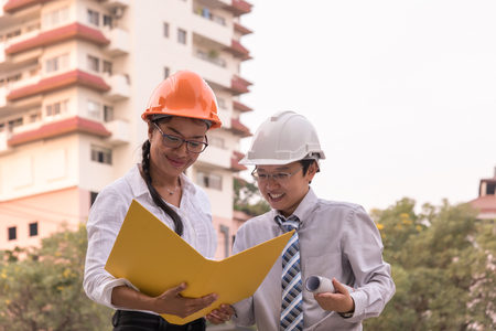 a creator: Smiling civil engineer holding blueprint paper construction plan talking with beautiful woman architect working in a construction site