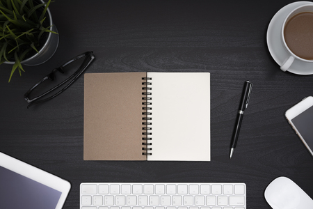Open blank notebook spiral with computer, office supplies and cup of coffee over black desk table, Top view with copy space Stock Photo