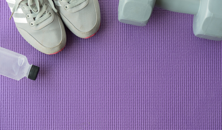 Fitness background with sport shoes, gray dumbbells and water over violet yoga mat in gym, Healthy and lifestyle concept