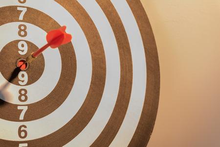 Red dart target arrow hitting on bullseye with sun light vintage style,metaphor to target marketing and business success concept Standard-Bild