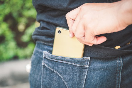 Thief stealing the mobile phone from the blue jeans pocket of a woman Standard-Bild