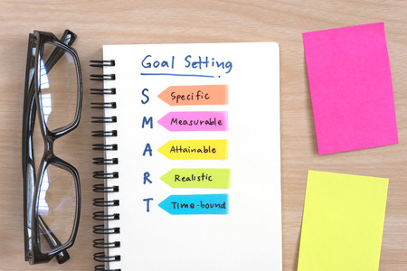 Hand writing definition for SMART goal setting on open notebook with eye glasses and colorful sticky note on office desk table