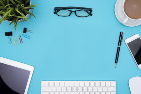 frame of office supplies, computer, pen, pencil, tablet, phone, flower, eye glasses and coffee cup on blue desk table, Top view with copy space