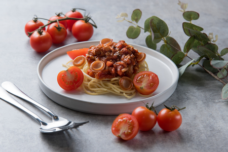 Spaghetti with tomato sauce and sausage in white plate on table