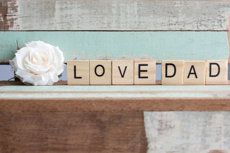 Love dad words with white rose on rustic vintage table over wooden retro background, Metaphor true love, Fathers day concept