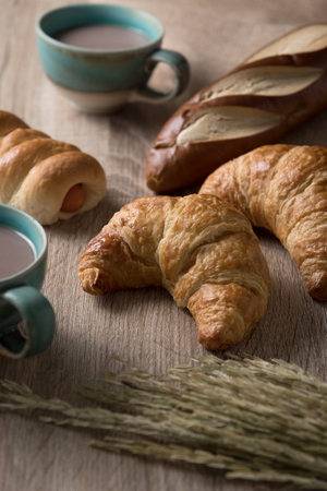 Croissants with bread and coffee cup on wooden background, vertical Standard-Bild
