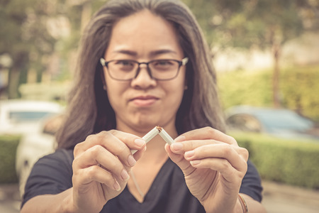 Woman break down cigarette and winning with addicted nicotine problems, stop smoking conceptual. Quitting from addiction concept.