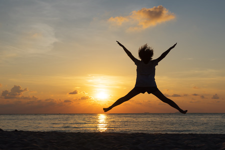 Freedom concept with silhouette young teenager happy and jump on a beautiful sunset at the beach Stock Photo