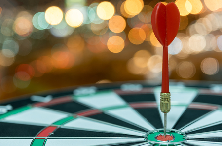 Red dart target arrow hitting on bullseye over bokeh light background vintage tone,metaphor to accuracy in business success concept