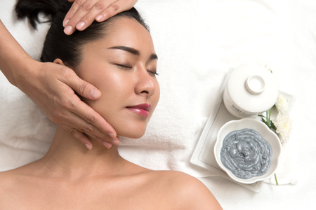 Close up of beautiful young asian woman lying with closed eyes and preparation face or head massage in spa or wellness, Beauty healthy lifestyle and relaxation concept