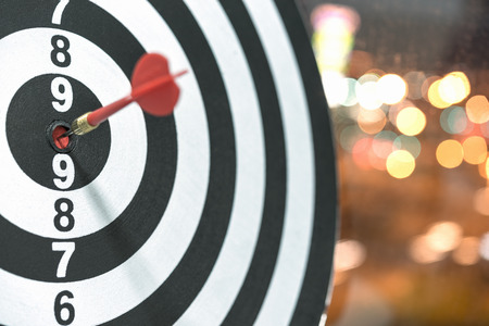 Red dart target arrow hitting on bullseye with bokeh background, Accuracy business success concept