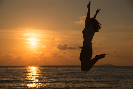 Freedom concept with young teenager happy and jump on a beautiful sunset at the beach