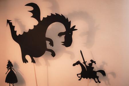 Sagome nere di drago, principessa e cavaliere con schermo luminoso luminoso di teatro delle ombre sullo sfondo.