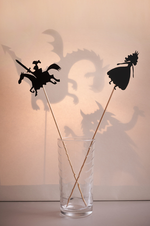shadow puppets: Shadow puppets of Princess and Knight with a soft glowing screen of shadow theatre and monsters shadows in the background.