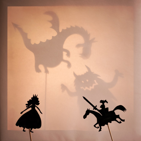 honorable: Beautiful Princess and Brave Knight. Black silhouettes of shadow puppets with a bright glowing screen of shadow theatre and monsters shadows in the background.