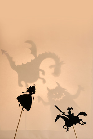 Pair of shadow puppets with monsters shadows on the bright glowing screen of shadow theatre in the background.