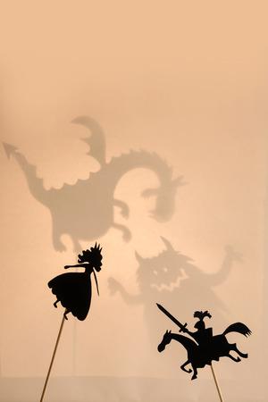 marioneta: Par de teatro de sombras con los monstruos sombras en la pantalla brillante brillante del teatro de sombras en el fondo.