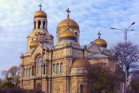 assumption: The Cathedral of the Assumption of the Virgin - the landmark of Varna, Bulgaria - in warm sunset light with cloudy sky in the background