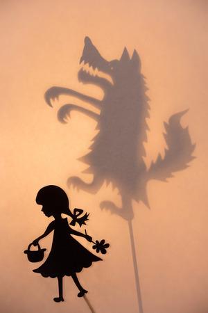 Piccola ombra fantoccio Cappuccetto Rosso e ombra del Big Bad Wolf sullo schermo incandescente luminoso di teatro delle ombre.
