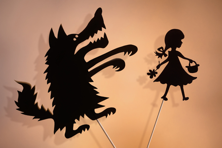 Little Red Riding Hood and the Big Bad Wolf shadow puppets and their shades on the soft glowing screen of shadow theater. Фото со стока