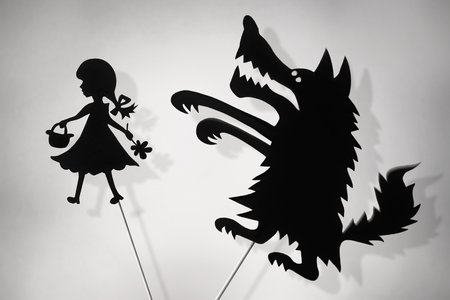 shadow puppets: Little Red Riding Hood and the Big Bad Wolf shadow puppets and their shades, copy spase background. Stock Photo
