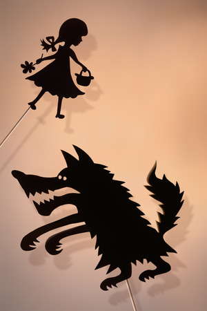 shadow puppets: Little Red Riding Hood and the Big Bad Wolf shadow puppets and their shades on the glowing screen of shadow theater. Copy space background.