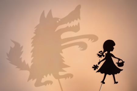 Little Red Riding Hood shadow puppet and the Big Bad Wolfs shade with the soft glowing screen of shadow theater in the background.