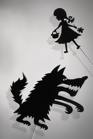 shadow puppets: Little Red Riding Hood and the Big Bad Wolf shadow puppets and their shades. Copy space background.