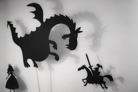 Schaduwpoppetjes van Dragon, Princess en Knight met zacht gloeiend scherm van schaduwtheater op de achtergrond