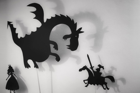 Shadow puppets of Dragon, Princess and Knight with soft glowing screen of shadow theater in the background Banco de Imagens