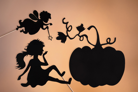 cinderella pumpkin: Fairy Godmother, Cinderella and Pumpkin shadow puppets on the soft glowing screen of shadow theater.