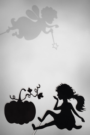 shadow puppets: Cinderella and Pumpkin shadow puppets and shades of Fairy Godmother on the screen of shadow theater, copy space background, black and white. Stock Photo