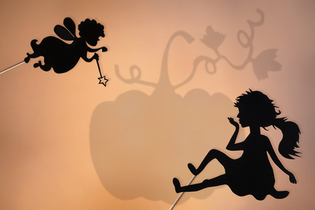 bad hair day: Fairy Godmother, Cinderella and Pumpkin shadow puppets on the soft glowing screen of shadow theater.
