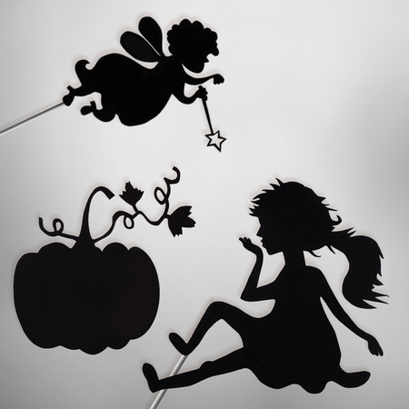 cinderella pumpkin: Fairy Godmother, Cinderella and Pumpkin shadow puppets on the screen of shadow theater, black and white.