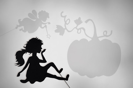 shadow puppets: Cinderella shadow puppet with Fairy Godmother and Pumpkin shadow silhouettes in the background.
