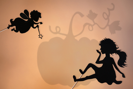 puppets: Fairy Godmother, Cinderella and Pumpkin shadow puppets, copy space background.