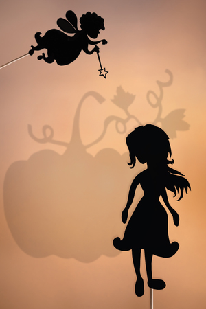 cinderella pumpkin: Fairy Godmother and Cinderella shadow puppets with the shade of big pumpkin in the background.