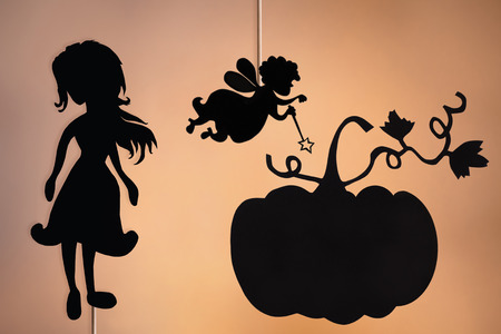 shadow puppets: Shadow puppets of Cinderella, Fairy Godmother and Pumpkin on the warm glowing screen of shadow theater. Stock Photo