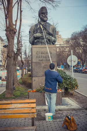 Varna, Bulgaria, March 22, 2017: A senior man cleans the statue of Stefan Karadzha located in the center of Varna.
