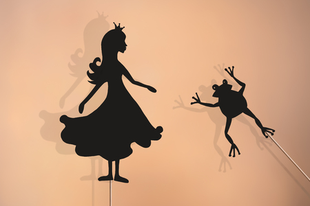 Shadow puppets of Princess and Frog with soft glowing screen of shadow theatre in the background.