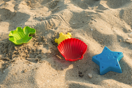 Childrens sand molds lie on the sea beach. Imagens